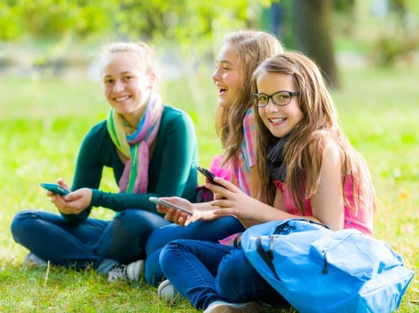 Teenager schoolgirls having fun with mobile phones